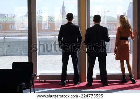 Group of businessmen: two men and a woman standing near big window with view of the Kremlin