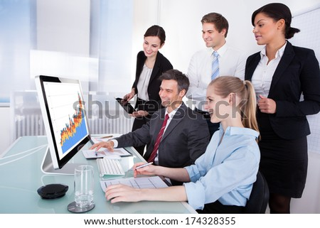 Group Of Businesspeople Analyzing Graph On Computer In Office