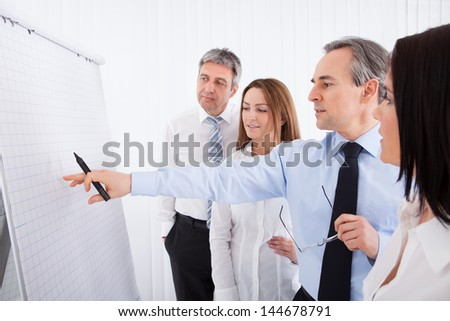 Group Of Businesspeople Discussing New Project On Whiteboard - stock photo