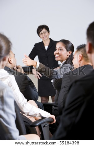 Group of businesspeople, focus on woman in audience speaking - stock photo