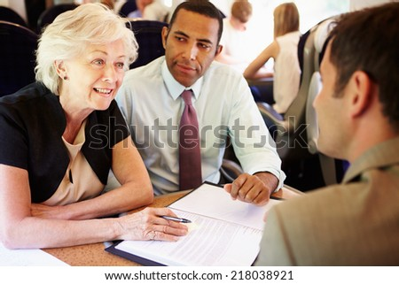 Group Of Businesspeople Having Meeting On Train - stock photo