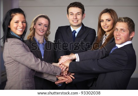 Group of 5 businesspeople hold their hands together, unity and teamwork concept - stock photo