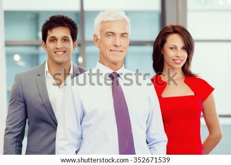 Group of businesspeople in office standing - stock photo