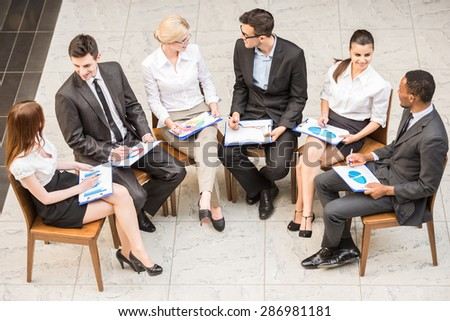 Group of  businesspeople in suits sitting in circle and discussing marketing results. - stock photo