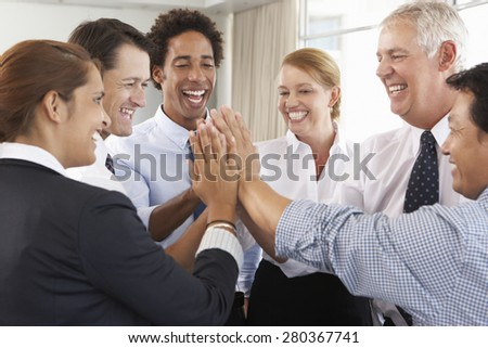 Group Of Businesspeople Joining Hands In Circle At Company Seminar - stock photo