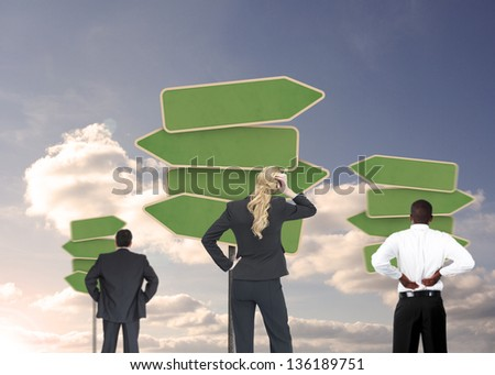 Group of businesspeople looking at empty signposts with blue cloudy sky