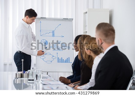 Group Of Businesspeople Looking At Young Businessman Giving Presentation In Meeting - stock photo
