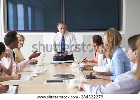 Group Of Businesspeople Meeting Around Boardroom Table - stock photo