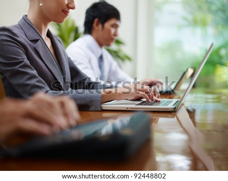 Group of businesspeople meeting in conference room and using laptop computers. Side view, copy space - stock photo