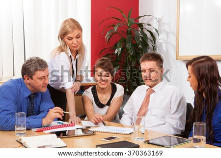 Group of businesspeople sitting at meeting table and working together - stock photo