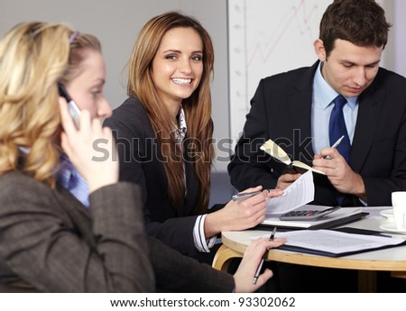 Group of 3 businesspeople sitting at table and work on paperwork - stock photo
