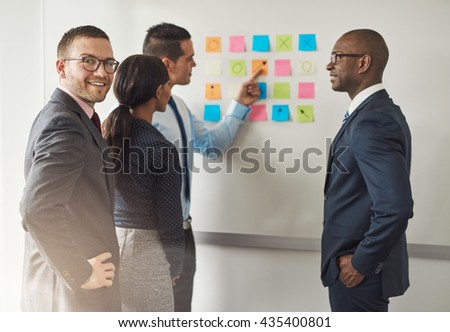 Group of businesspeople solving a puzzle on colorful memo notes on a wall with a young male executive at the rear turning to smile at the camera - stock photo