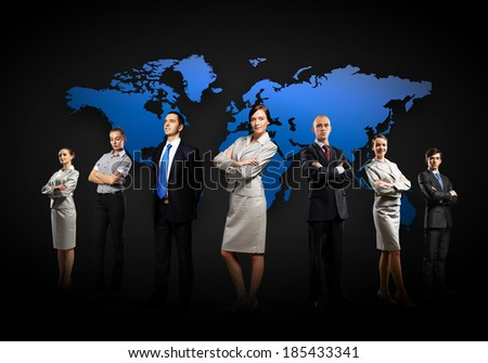 Group of businesspeople standing together against a world map background - stock photo