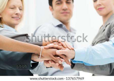 Group Of Businesspeople With Stacked Hands Showing Unity and Teamwork - stock photo