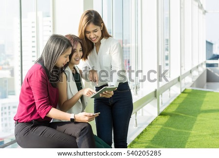 Group Of Businesswomen brainstorm Meeting with looking at tablet In the modern creative Office, business technology concept