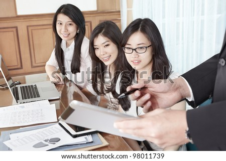 Group of businesswomen looking at the tablet held by a supervisor hand - stock photo