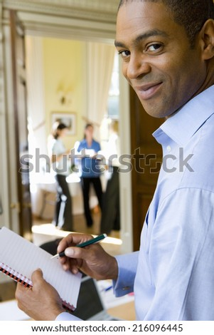 Group of businesswomen taking break from training course, portrait of man with notepad