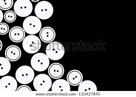 Group of buttons for clothing on a black background. - stock photo