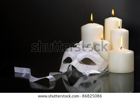 Group of candles and carnival mask over black background