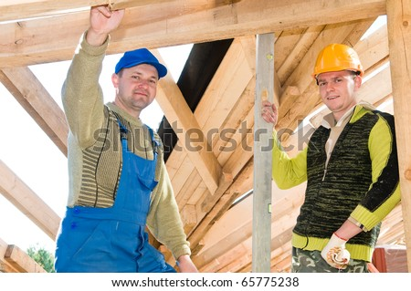 group of carpenters roofers workers in uniform at roofing works with level - stock photo
