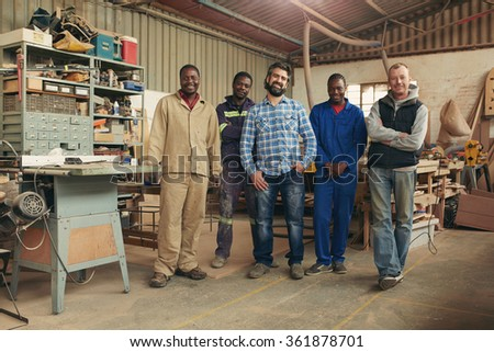 Group of carpenters smiling at the camera - stock photo