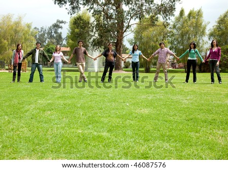 Group of casual people outdoors holding hands - stock photo
