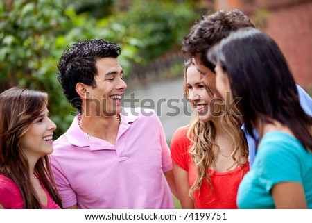 Group of casual young people talking outdoors - stock photo