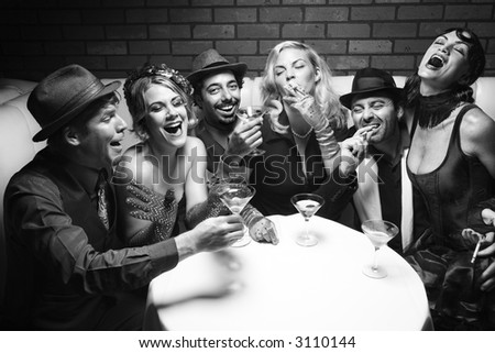 Group of Caucasian prime adult retro males and females sitting at table in lounge laughing. - stock photo
