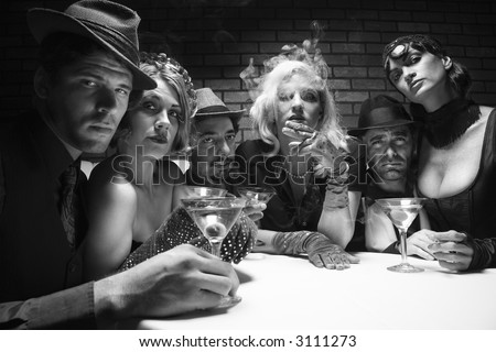 Group of Caucasian prime adult retro males and females sitting at table in lounge looking at viewer. - stock photo