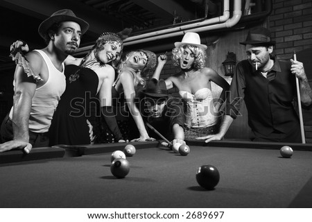 Group of Caucasian prime adult retro males and females trying to distract man as he takes pool shot. - stock photo