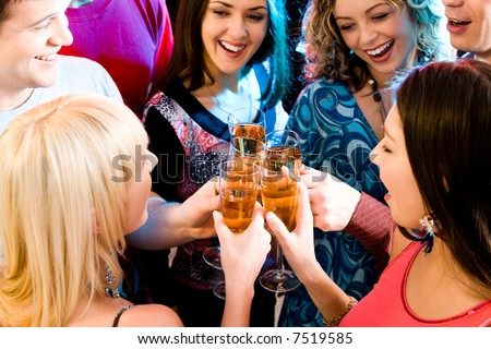 Group of champagne flutes in people's hands making a toast