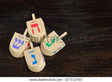 Group of Chanukah wooden dreidels on dark wood grain texture background, top down view. 4 large wood dreidels with colorful Hebrew letters nun, gimel, hey, shin. Copyspace.   - stock photo