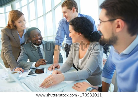 Group of cheerful business partners planning work at meeting - stock photo