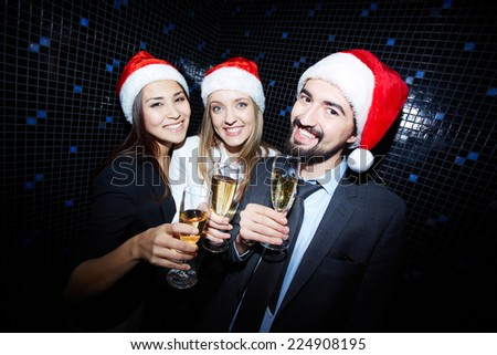 Group of cheerful business people in Santa caps toasting with champagne in nightclub  - stock photo