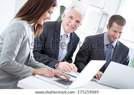 Group of cheerful business people working at their office together.