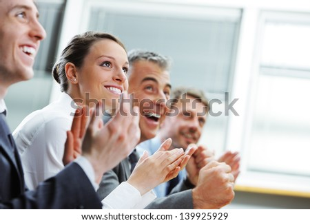 Group of cheerful businesspeople sitting in a row on a presentation and clapping - stock photo