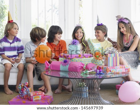 Group of cheerful children sitting on sofa at birthday party - stock photo