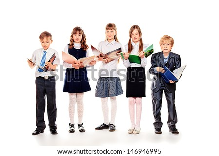 Group of cheerful children standing with books. Isolated over white.