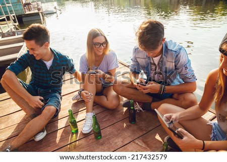 Group Of Cheerful Friends Having Fun Near Lake Using Digital Tablet - stock photo