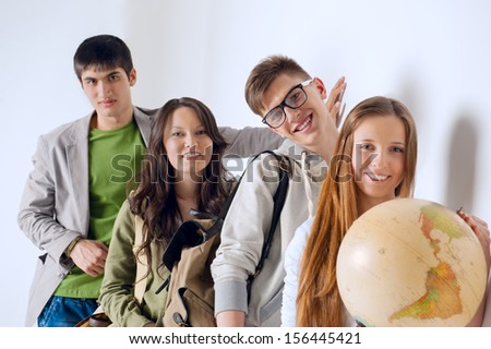 Group of cheerful happy students holding world globe and looking at camera leaning on white wall at campus. International education concept - stock photo
