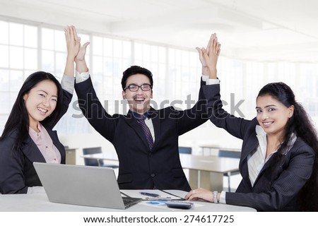 Group of cheerful multi-ethnic business team celebrate their victory in the office - stock photo