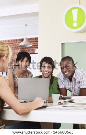 Group of cheerful multiethnic business people using laptop in meeting room - stock photo