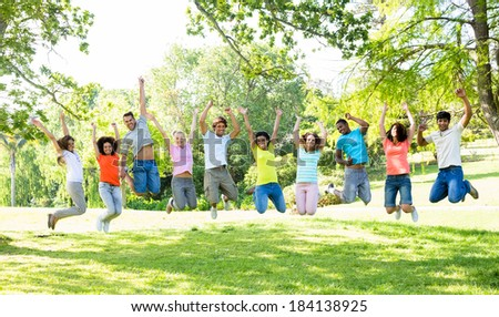 Group of cheerful multiethnic friends jumping in park - stock photo