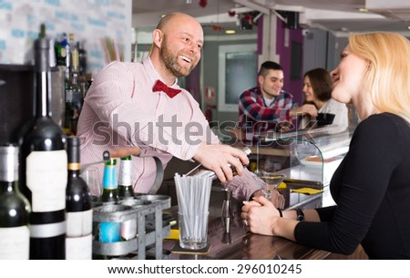Group of cheerful positive young adults hanging out in bar - stock photo