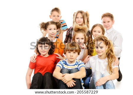 Group of cheerful schoolchildren sitting together. Isolated over white.
