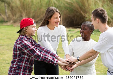 Group of cheerful smiling teenage friends spending time outdoors  - stock photo