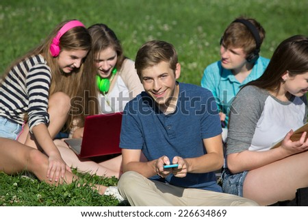 Group of cheerful students texting and studying