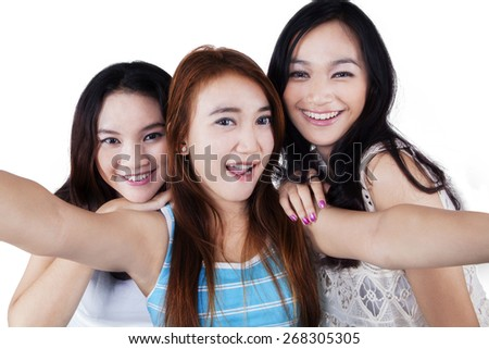 Group of cheerful teenage girls taking a selfie together in the studio, isolated over white - stock photo