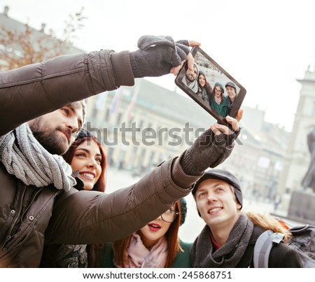 Group Of Cheerful Tourists Taking Selfie Using Digital Tablet - stock photo