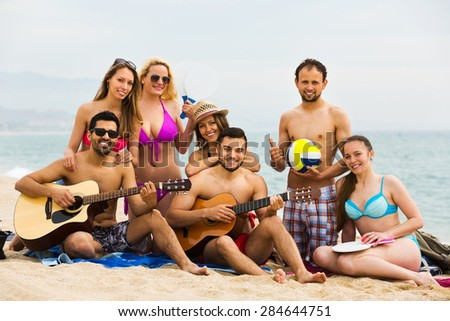 Group of cheerful young friends relaxing on sand at beach with guitar. Selective focus